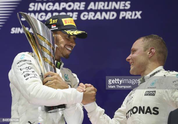 Race winner Lewis Hamilton of Great Britain and Mercedes GP shakes hands with third place finisher Valtteri Bottas of Finland and Mercedes GP on the...