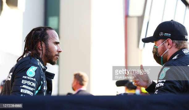 Race winner Lewis Hamilton of Great Britain and Mercedes GP speaks to second placed Valtteri Bottas of Finland and Mercedes GP in parc ferme during...