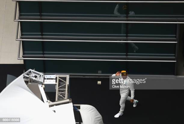 Race winner Lewis Hamilton of Great Britain and Mercedes GP walks to the podium during the Formula One Grand Prix of China at Shanghai International...