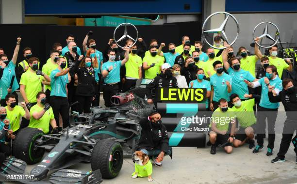 Race winner Lewis Hamilton of Great Britain and Mercedes GP celebrates winning a 7th F1 World Drivers Championship with his team in the Pitlane after...