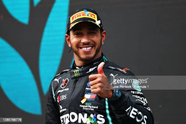 Race winner Lewis Hamilton of Great Britain and Mercedes GP celebrates winning a 7th F1 World Drivers Championship on the podium during the F1 Grand...