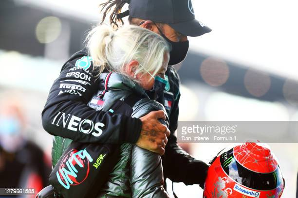 Race winner Lewis Hamilton of Great Britain and Mercedes GP celebrates with his trainer Angela Cullen after being presented with a helmet of Michael...