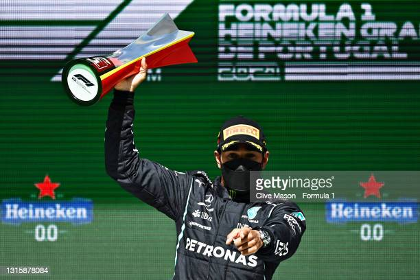 Race winner Lewis Hamilton of Great Britain and Mercedes GP celebrates with his trophy on the podium during the F1 Grand Prix of Portugal at...