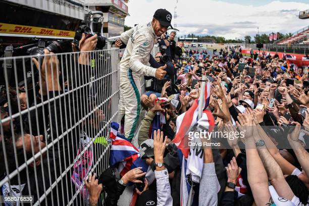Race winner Lewis Hamilton of Great Britain and Mercedes GP celebrates with his fans on the pit wall after the Spanish Formula One Grand Prix at...