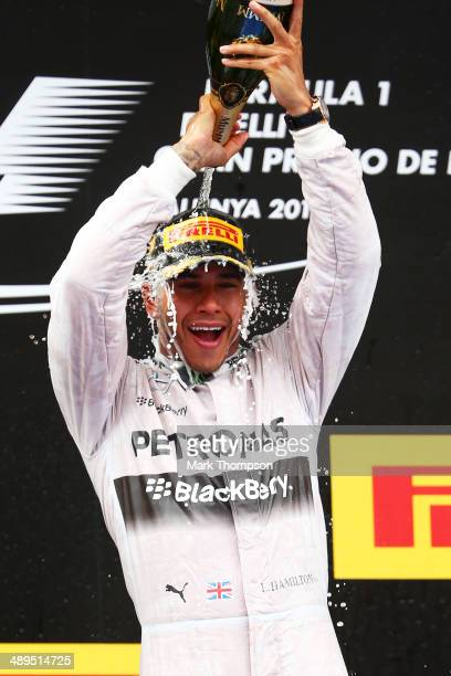 Race winner Lewis Hamilton of Great Britain and Mercedes GP celebrates with champagne on the podium during the Spanish Formula One Grand Prix at...