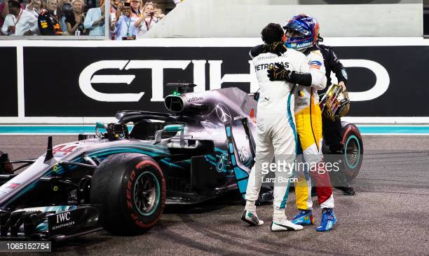 Race winner Lewis Hamilton of Great Britain and Mercedes GP celebrates with Fernando Alonso of Spain and McLaren F1 on track during the Abu Dhabi...
