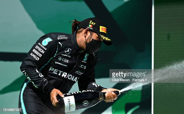 Race winner Lewis Hamilton of Great Britain and Mercedes GP celebrates with sparkling wine on the podium during the F1 Grand Prix of Portugal at...