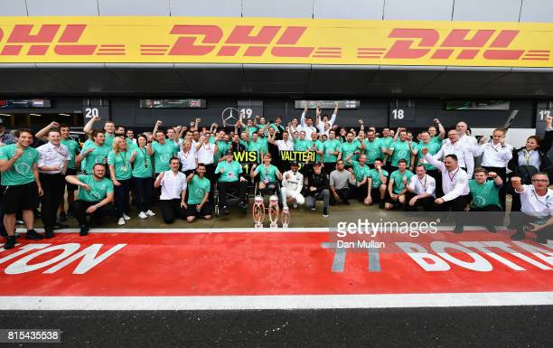 Race winner Lewis Hamilton of Great Britain and Mercedes GP celebrates with Valtteri Bottas of Finland and Mercedes GP Billy Monger and his team...
