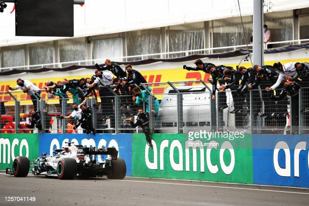 Race winner Lewis Hamilton of Great Britain driving the Mercedes AMG Petronas F1 Team Mercedes W11 passes his team celebrating on the pitwall during...