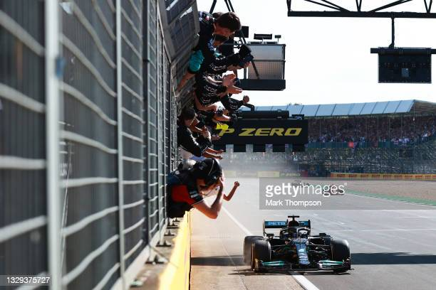 Race winner Lewis Hamilton of Great Britain driving the Mercedes AMG Petronas F1 Team Mercedes W12 passes his team celebrating on the pitwall during...