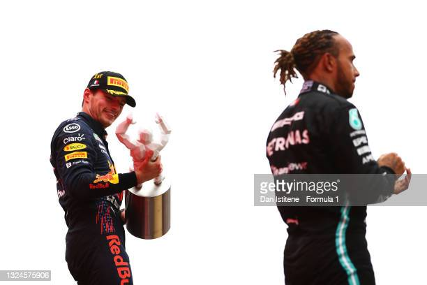 Race winner Max Verstappen of Netherlands and Red Bull Racing celebrates on the podium next to second placed Lewis Hamilton of Great Britain and...