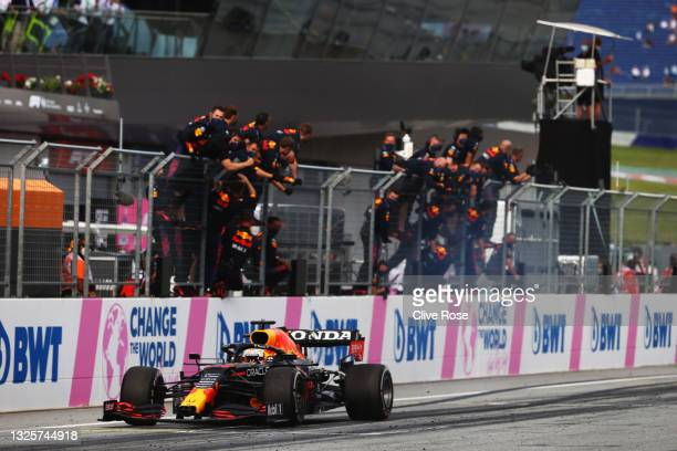 Race winner Max Verstappen of the Netherlands driving the Red Bull Racing RB16B Honda takes the chequered flag as his team celebrate on the pitwall...