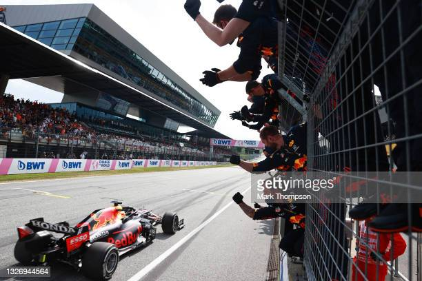 Race winner Max Verstappen of the Netherlands driving the Red Bull Racing RB16B Honda passes his team celebrating on the pitwall during the F1 Grand...
