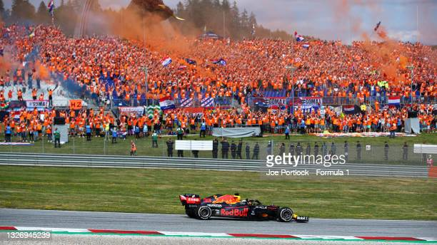 Race winner Max Verstappen of the Netherlands driving the Red Bull Racing RB16B Honda past a grandstand full of his fans celebrating during the F1...
