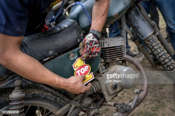 A race winner puts the memorial sticker into his Minsk motorcycle after an offroad race on November 5 2017 in Hanoi Vietnam A new generation of...