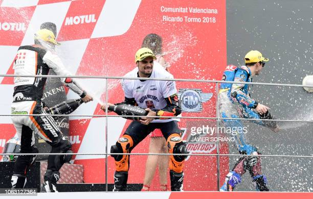 Race winner Red Bull KTM Ajo's Portuguese rider Miguel Oliveira celebrates on the podium with second placed Swiss Innovative Investors' Spanish rider...