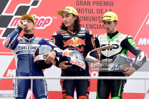 Race winner Red Bull KTM Ajo's Turkish rider Can Oncu celebrates on the podium with second placed Del Conca Gresini Racing Moto3's Spanish rider...