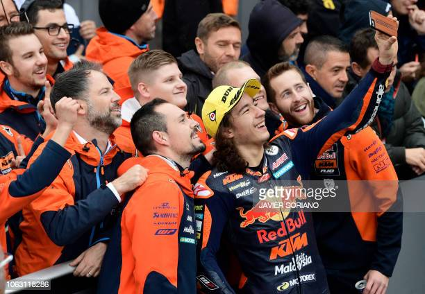 Race winner Red Bull KTM Ajo's Turkish rider Can Oncu takes a selfie photo as he celebrates with teammates winning the Moto3 race of the Valencia...