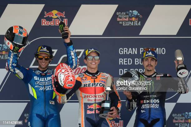 Race winner Repsol Honda Team's Spanish rider Marc Marquez celebrates on the podium with second placed Suzuki Ecstar's Spanish rider Alex Rins and...