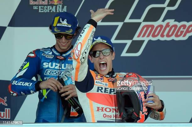Race winner Repsol Honda Team's Spanish rider Marc Marquez celebrates on the podium with second placed Suzuki Ecstar's Spanish rider Alex Rins after...