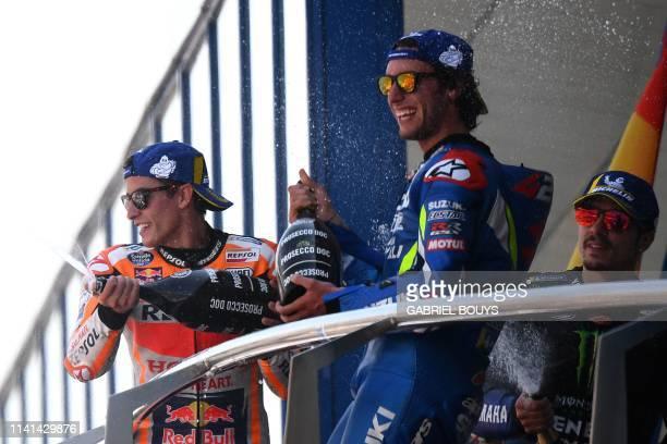 Race winner Repsol Honda Team's Spanish rider Marc Marquez celebrates on the podium with Suzuki Ecstar's Spanish rider Alex Rins and Monster Energy...