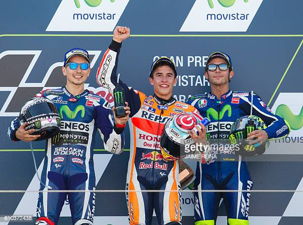 Race winner Repsol Honda's Spanish rider Marc Marquez celebrates on the podium between second placed Yamaha Team's Spanish rider Jorge Lorenzo and...