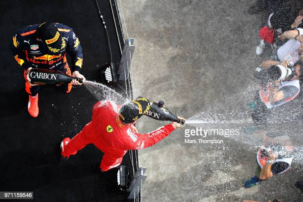 Race winner Sebastian Vettel of Germany and Ferrari and third place finisher Max Verstappen of Netherlands and Red Bull Racing celebrate on the...