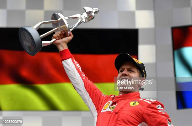 Race winner Sebastian Vettel of Germany and Ferrari celebrates on the podium during the Formula One Grand Prix of Belgium at Circuit de...