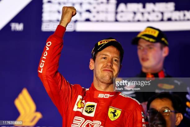 Race winner Sebastian Vettel of Germany and Ferrari celebrates on the podium during the F1 Grand Prix of Singapore at Marina Bay Street Circuit on...
