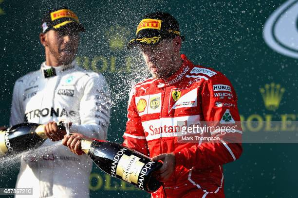 Race winner Sebastian Vettel of Germany and Ferrari celebrates on the podium with second place finisher Lewis Hamilton of Great Britain and Mercedes...