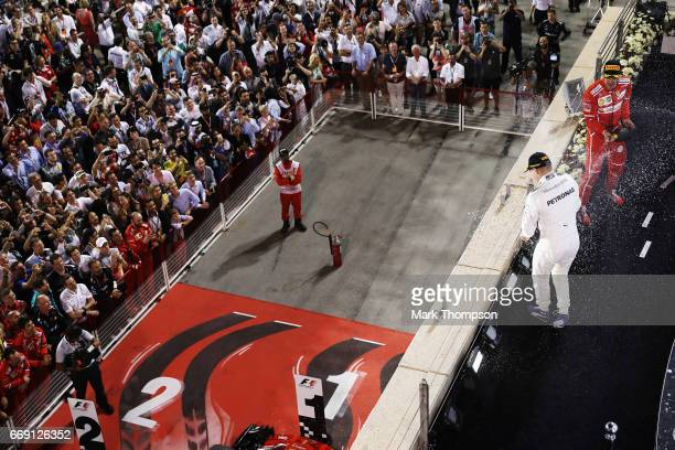 Race winner Sebastian Vettel of Germany and Ferrari celebrates on the podium with third placed Valtteri Bottas of Finland and Mercedes GP during the...