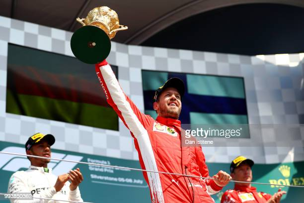 Race winner Sebastian Vettel of Germany and Ferrari celebrates on the podium during the Formula One Grand Prix of Great Britain at Silverstone on...