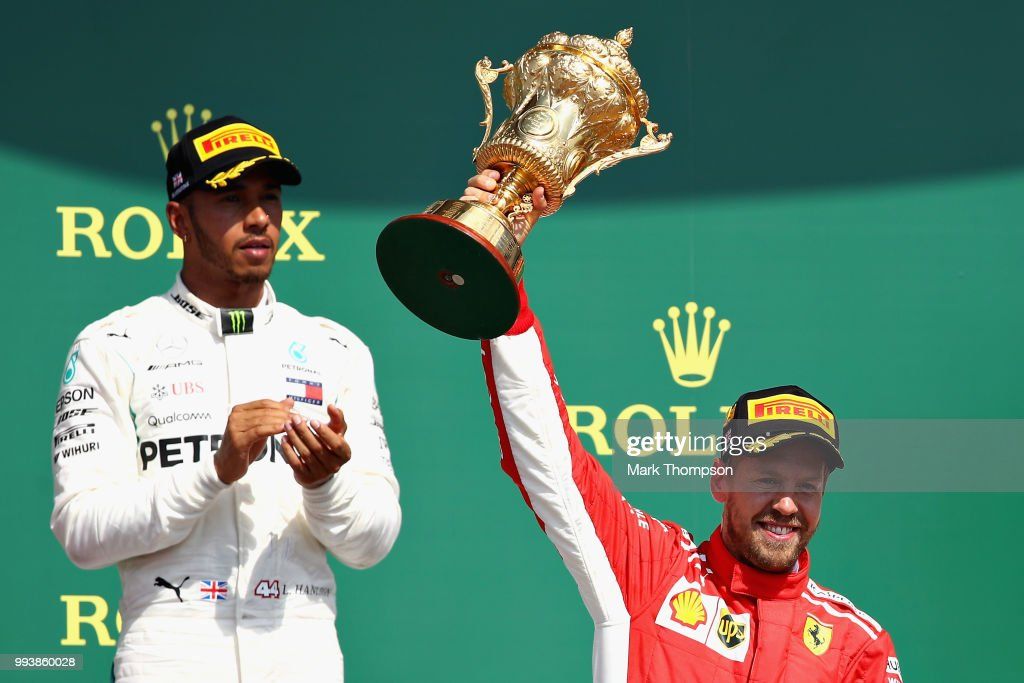Race winner Sebastian Vettel of Germany and Ferrari celebrates on the podium as second place finisher Lewis Hamilton of Great Britain and Mercedes GP looks on during the Formula One Grand Prix of Great Britain at Silverstone on July 8, 2018 in Northampton, England.