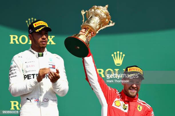 Race winner Sebastian Vettel of Germany and Ferrari celebrates on the podium as second place finisher Lewis Hamilton of Great Britain and Mercedes GP...