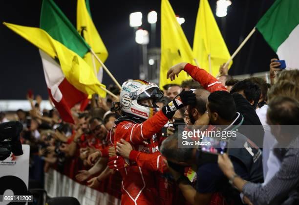 Race winner Sebastian Vettel of Germany and Ferrari celebrates with his team in parc ferme during the Bahrain Formula One Grand Prix at Bahrain...