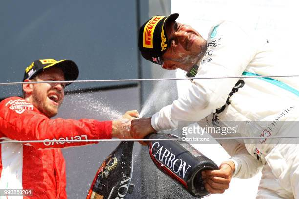 Race winner Sebastian Vettel of Germany and Ferrari celebrates with second placed finisher Lewis Hamilton of Great Britain and Mercedes GP on the...