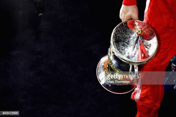 Race winner Sebastian Vettel of Germany and Ferrari hold his trophy on the podium during the Bahrain Formula One Grand Prix at Bahrain International...