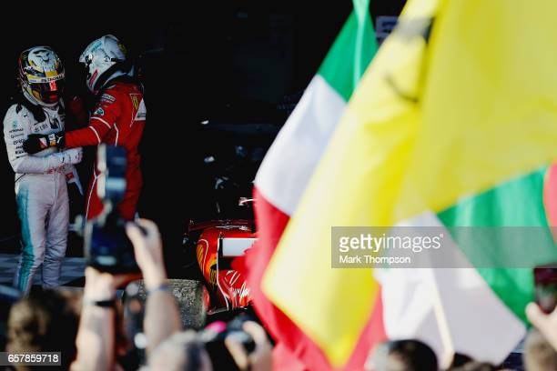 Race winner Sebastian Vettel of Germany and Ferrari is congratulated by second place Lewis Hamilton of Great Britain and Mercedes GP in parc ferme...