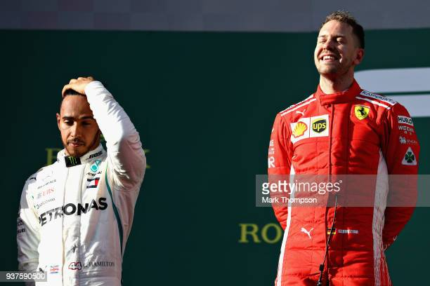 Race winner Sebastian Vettel of Germany and Ferrari looks ecstatic as second placed Lewis Hamilton of Great Britain and Mercedes GP looks dejected on...