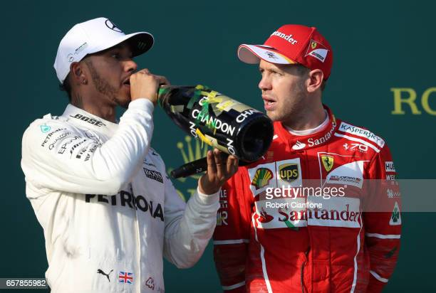 Race winner Sebastian Vettel of Germany and Ferrari talks with second place Lewis Hamilton of Great Britain and Mercedes GP on the podium during the...