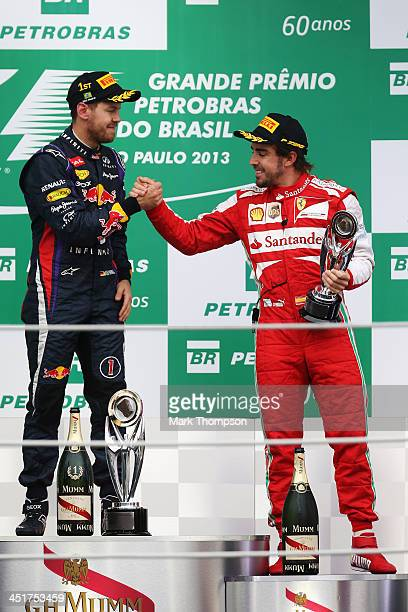 Race winner Sebastian Vettel of Germany and Infiniti Red Bull Racing celebrates on the podium with third placed Fernando Alonso of Spain and Ferrari...