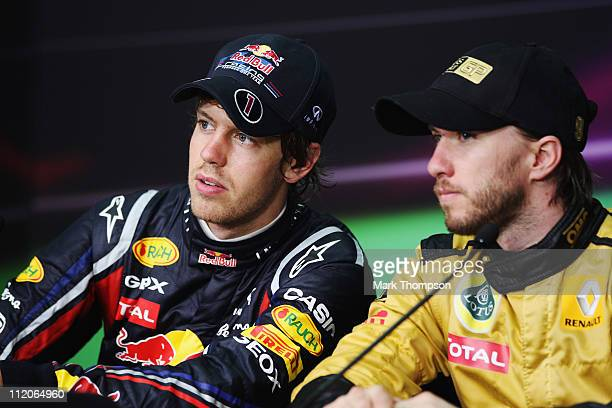 Race winner Sebastian Vettel of Germany and Red Bull Racing and third placed Nick Heidfeld of Germany and Renault attend the drivers press conference...