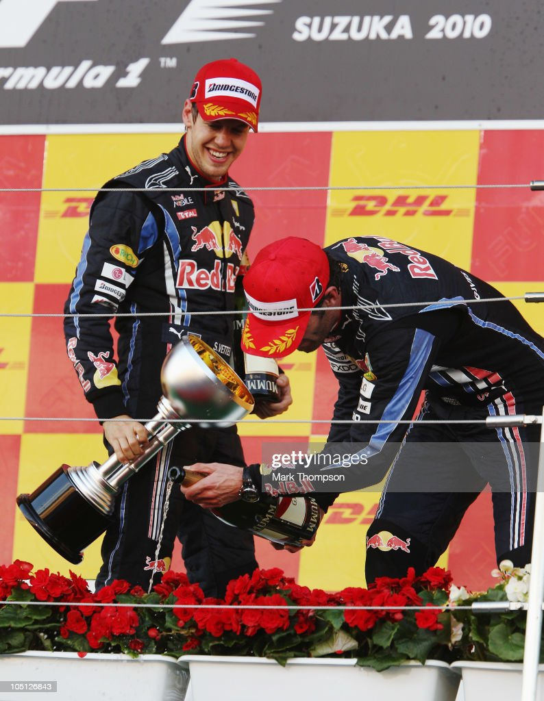 Race winner Sebastian Vettel (L) of Germany and Red Bull Racing looks on as second placed team mate Mark Webber (R) of Australia and Red Bull Racing waters the podium flowers with champagne after the Japanese Formula One Grand Prix at Suzuka Circuit on October 10, 2010 in Suzuka, Japan.