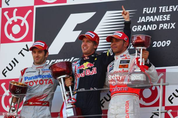 Race winner Sebastian Vettel of Germany and Red Bull Racing celebrates on the podium with second placed Jarno Trulli of Italy and Toyota and third...