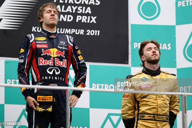 Race winner Sebastian Vettel of Germany and Red Bull Racing celebrates with third placed Nick Heidfeld of Germany and Renault on the podium after the...