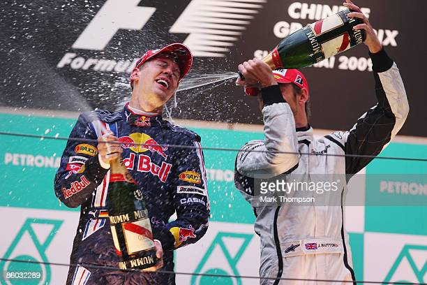Race winner Sebastian Vettel of Germany and Red Bull Racing celebrates with third placed Jenson Button of Great Britain and Brawn GP on the podium...