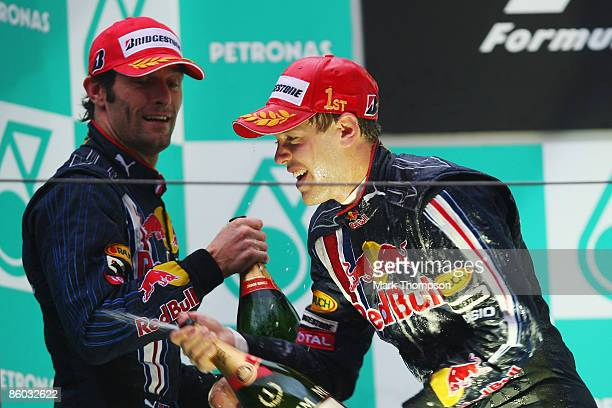 Race winner Sebastian Vettel of Germany and Red Bull Racing celebrates with second placed team mate Mark Webber of Australia and Red Bull Racing on...