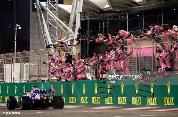 Race winner Sergio Perez of Mexico driving the Racing Point RP20 Mercedes takes the flag as teammates celebrate during the F1 Grand Prix of Sakhir at...