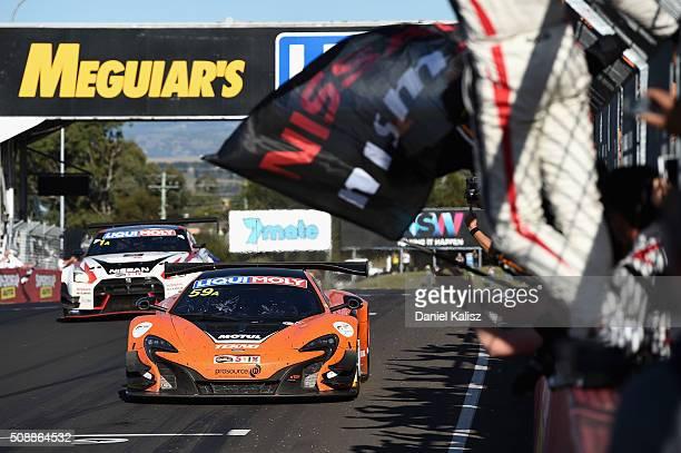 Race winner Shane van Gisbergen driver of the Tekno Autosport McLaren 650S crosses the finish line to win the Bathurst 12 Hour Race at Mount Panorama...
