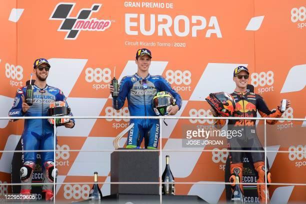 Race winner Suzuki Ecstar's Spanish rider Joan Mir celebrates on the podium with Suzuki Ecstar's Spanish rider Alex Rins and Red Bull KTM Factory...